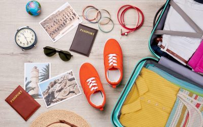 Different travelling accessories, packed suitcase. Summer holiday background.